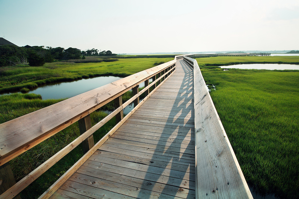 A public dock leads out into wetlands of Surf City NC, over the marsh grass.