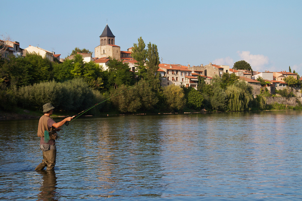Artur Frenandes casting his fly out onto the Allier with the city of Pont-du-Chateau as a backdrop. Pont-du-Chateau, France.