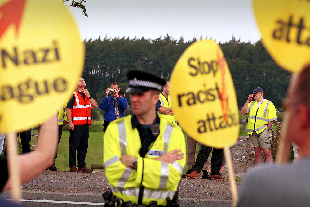 The British National Party (BNP) supporters are seperated from a handful of demonstrators from the Anti Nazi League by the police. The BNP held it's annual Red White and Blue festival in field at Sawley near the Lancashire town of Clitheroe, just north of Burnley. The BNP have 3 local councillors sitting on the Burnley city council, elected during the 2002 Local council Elections..