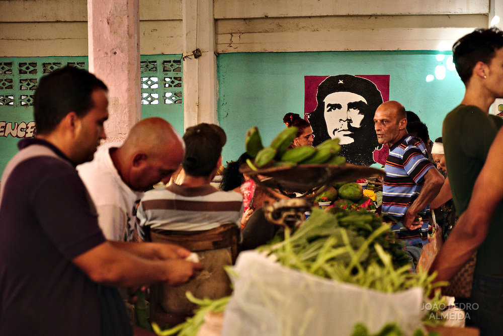 Stands selling fresh produce inside Cienfuegos market, with the always present image of Che Guevara