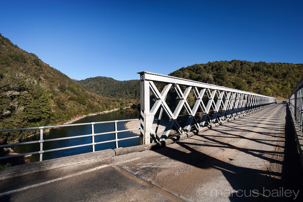car approaching single lane iron bridge which spans the buller river, west coast, new zealand