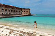 A girl wades in the calm clear water at Dry Tortugas National park on a family vacation in Florida. Dry Tortugas can be visited on a day trip by ferry or seaplane from Key West. Model released photo.