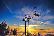 Skiers on Chairlift above inversion clouds at sunset at Whitefish Mountain Resort in Montana