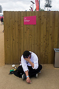 A smoking worker enjoys a rest and cigarette in a designated smoking zone area in the Olympic Park during the London 2012 Olympics. This land was transformed to become a 2.5 Sq Km sporting complex, once industrial businesses and now the venue of eight venues including the main arena, Aquatics Centre and Velodrome plus the athletes' Olympic Village. After the Olympics, the park is to be known as Queen Elizabeth Olympic Park.