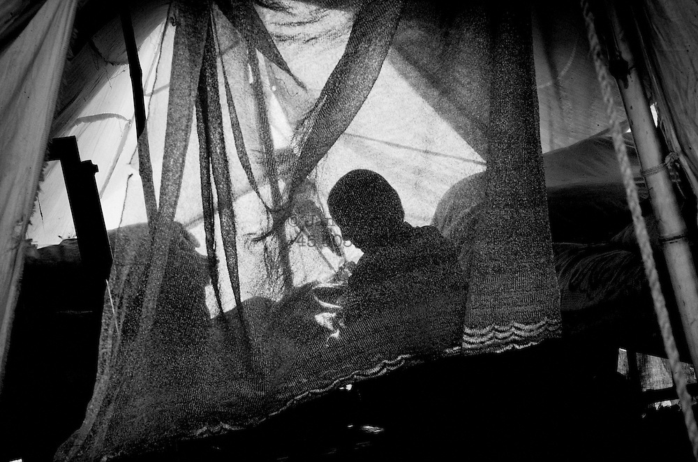 a young woman taking care of her sick child in an outdoor hospital tentcamp in Mansehra.<br /> Manshera, Nov 2005