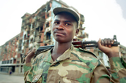 """An Angolan soldier known as """"Bernardo"""" stands in the center of a town in the interior region where fighting between the rebels and government forces left the edifices in ruins. Angola's brutal 26 year-civil war has displaced around two million people - about a sixth of the population - and 200 die each day according to United Nations estimates..(Photo by Ami Vitale)"""