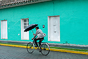 A man rides his bicycle with an umbrella past a brightly painted Caribbean style building along the Venustiano Carranza in Tlacotalpan, Veracruz, Mexico. The tiny town is painted a riot of colors and features well preserved colonial Caribbean architectural style dating from the mid-16th-century.
