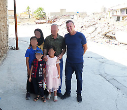 "EXCLUSIVE: POSTCARD FROM MOSUL, A BRITISH DAD HAS BECOME THE FIRST PERSON TO TAKE A HOLIDAY IN THE RUINS OF ISLAMIC STATE – AND HE'S EVEN INTERVIEWED AN ISIS BRIDE A married British dad has become the first person to take a HOLIDAY in the ruins of the ISLAMIC STATE. Without visas and in constant danger of kidnapping, beatings from militia, and even death, Andy Drury took a £4,000 three-day mini break in what was once Hell on Earth. Dad-of-four Andy, 53, has brought back never-before-seen photographs of the devastated former ISIS Caliphate centre Mosul, in Northern Iraq. And amidst shocking apocalyptic scenes the innocent survivors and their families have spoken to him about trying to rebuild their lives in the rubble. The building firm owner, from Guildford, Surrey, even gained access to an ISIS bride whose husband and two sons are all believed to have fought for the death cult. Andy has spent the last 20 years touring areas of the planet most us don't dare tread and it's not the first time he's been to Iraq. In 2016 he narrowly escaped death after visiting the frontline in Bashiir, south of Kirkuk, where he spent time with Kurdish soldiers fighting ISIS. During that encounter Andy, who doesn't wear a bulletproof vest or helmet, was shot at by Islamic State but luckily escaped unharmed. Andy, who lives with his wife and children, said his biggest reason for returning to the dangerous region last month was to see if the men he spent time with on the front line were still alive. His three-day tour was split into the former front line near Kirkuk on day one, the former ISIS stronghold Mosul on day two, and a last day visiting a refugee camp and interviewing an ISIS wife. Andy said: ""I must be the first person to be have been a tourist in the ruins of Islamic State. ""My fixer Ammar (not his real name) was right on the front line for the taking back of Mosul, taking reporters in there. ""But he said he is more scared with me, with the news reporters he"