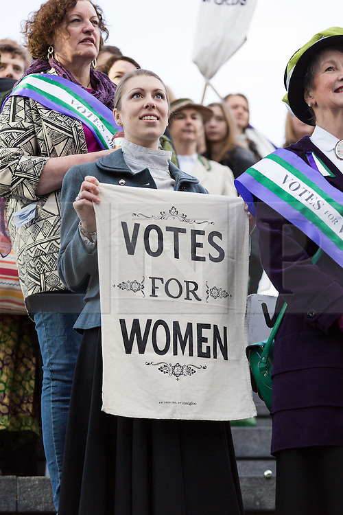 """© Licensed to London News Pictures. 08/03/2015. London, UK. People dressed as suffragettes at the """"Walk In Her Shoes"""" event to mark International Women's Day at The Scoop amphitheatre on the south bank in London. Photo credit : Vickie Flores/LNP"""