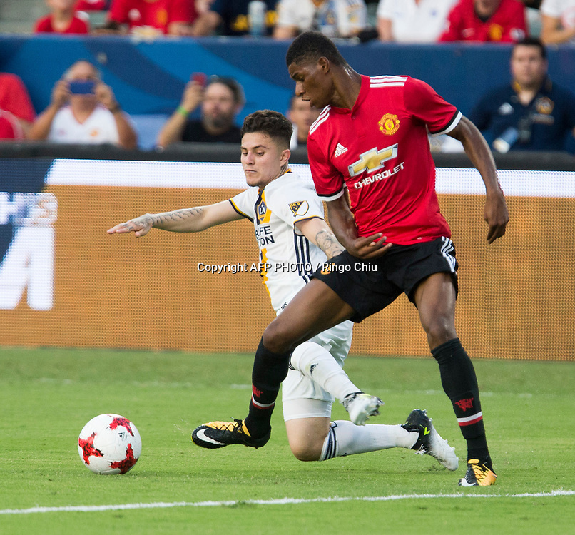 Manchester United Marcus Rashford, right, and Los Angeles Galaxy Raul Mendiola battle for the ball during the first half of a national friendly soccer game at StubHub Center on July 15, 2017 in Carson, California.   AFP PHOTO / Ringo Chiu