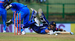 August 27, 2017 - Kandy, Sri Lanka - Sri Lankan cricketer Dinesh Chandimal (R) dives in as India's MS Dhoni removes the bails in an unsuccessful run-out  opportunity during the 3rd One Day International cricket match between Sri Lanka and India at the Pallekele international cricket stadium at Kandy, Sri Lanka on Sunday 27 August 2017. (Credit Image: © Tharaka Basnayaka/NurPhoto via ZUMA Press)