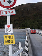 One of New Zealand's many one-lane bridges, with a crossing car, this one spanning the Waimakariri River, near Arthurs Pass.