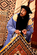 Propritor and chief carpet salesman at the Maison Berbere, Tinerhir, Morocco, lifts a carpet by the corner and discusses its qualities.