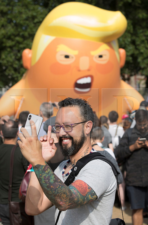 © Licensed to London News Pictures. 13/07/2018. London, UK. A man takes a selfie as a giant inflatable balloon depicting President Trump as a baby in a nappy is flown over Parliament Square. President Trump is on the second day of a four day visit to the UK. Photo credit: Peter Macdiarmid/LNP