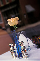 Sidewalk restaurant table flower vase silver salt and pepper shakers, napkin.