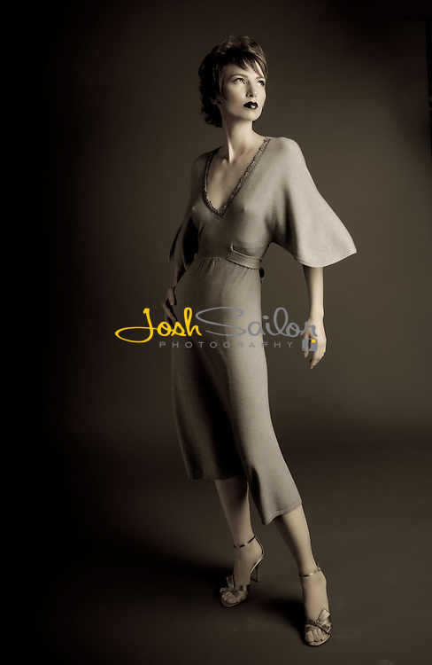 Elegant fashion model on dark sweep wearing a flowing gown.