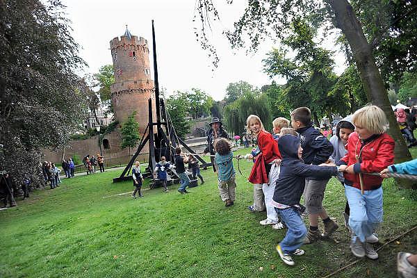 Nederland, Nijmegen, 28-8-2011Tijdens het Geboeders van Limburg festival staat een grote katapult in het Kronenburgerpark. Hij kan zakken water tegen de oude kruittoren schieten.Kinderen helpen bij het spannen van het apparaat.In de late Middeleeuwen (1350-1450) was Nijmegen met de Valkenhofburcht de belangrijkste stad in hertogdom Gelre. De drie rond 1380 in Nijmegen geboren gebroeders van Limburg waren beroemde tekenaars en kopiisten die vooral aan het franse hof furore maakten. Met het Gebroeders van Limburg festival eert de stad hen. Foto: Flip Franssen