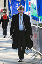 © Licensed to London News Pictures. 30/01/2019. London, UK. John Whittingdale MP seen walking through Westminster by flags belonging to Brexit demonstrators. Photo credit : Tom Nicholson/LNP