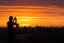 Primrose Hill, London, September 27th 2016. A man photographs the sunrise on Primrose Hill as dawn breaks over London. ©Paul Davey<br /> FOR LICENCING CONTACT: Paul Davey +44 (0) 7966 016 296 paul@pauldaveycreative.co.uk