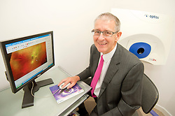Mike Broadhurst of Broadhurst Optometrists with the Optos Optomax Machine in his new shop in Preston which opened on Saturday ..18 August 2012.Image © Paul David Drabble