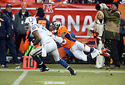 Indianapolis Colts wide receiver Donte Moncrief (10) catches a second quarter pass for a first down at the Denver Broncos 8 yard line while Denver Broncos cornerback Chris Harris, Jr. (25) hangs on for the tackle during the NFL week 19 AFC Divisional Playoff football game against the Denver Broncos on Sunday, Jan. 11, 2015 in Denver. The Colts won the game 24-13. ©Paul Anthony Spinelli