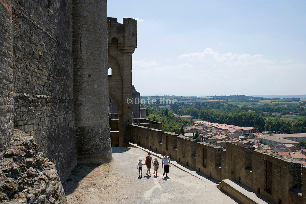 a family walking a long the walls of the castle at La Cite Carcassonne France