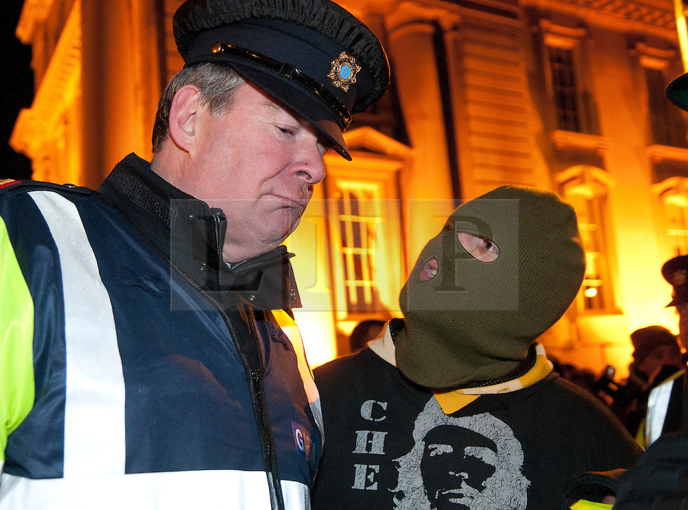 """© under license to London News Pictures.  07/12/2010. A man """"with three kids under four"""" argues with a policeman about his thoughts on the budget on Merrion Street in Dublin, Ireland on 7/12/2010. Photo credit should read Michael Graae/London News Pictures"""