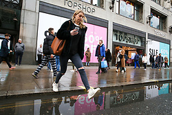 "© Licensed to London News Pictures. 23/12/2018. London, UK. A woman jumps over a puddle of water outside TopShop with a large window display showing ""Sale 60% Off"". Last minute Christmas shoppers take advantage of pre-Christmas bargains in London's Oxford Street. Fewer shoppers have been reported shopping in Britain's high streets as online sales increase. Photo credit: Dinendra Haria/LNP"