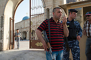 Kurdish police and local protection militias guard the entrance to the Saint Yohana Church in the Christian town of Karaqosh located on the Nineveh Plain just 20 kilometers from Mosul, one of the most violent cities in Iraq and the scene of numerous attacks against the Christian population. Karaqosh, Iraq. 18/04/2014.