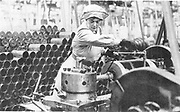 World War I - 1914-1918.  After conscription in 1916, women took over many civilian jobs.  British woman munitions worker operating a lathe.
