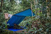 Après une journée de marche, les rangers montent le camp : un feu pour cuisiner et une bâche pour passer la nuit. Protection sommaire contre les intenses pluies tropicales.
