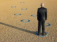 Businessman standing in hoops in desert back view full length
