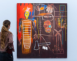 "© Licensed to London News Pictures. 01/11/2016. London, UK. A staff member views ""Air Power"" by Jean-Michel Basquiat, est. GBP2.5-3.5m. The first look of ""Bowie / Collector"", artworks from the late David Bowie's personal art collection, ahead of their sale later this month at Sotheby's. Photo credit : Stephen Chung/LNP"