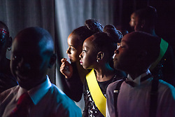 "E. Benjamin Oliver dancers peek at the audience before the competition begins.  Dancing Classrooms Virgin Islands students compete in ""Colors of the Rainbow"" team match competition at Reichhold Center for the Arts.  St. Thomas, USVI.  9 May 2015.  © Aisha-Zakiya Boyd"