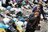 ITALY, NAPLES : Women walk through uncollected garbage downtown Naples in the historic Spanish district on November 22, 2010. Naples latest garbage emergency is getting worst day after day and piles of garbage are seen all over the italian souther city. AFP PHOTO / ROBERTO SALOMONE