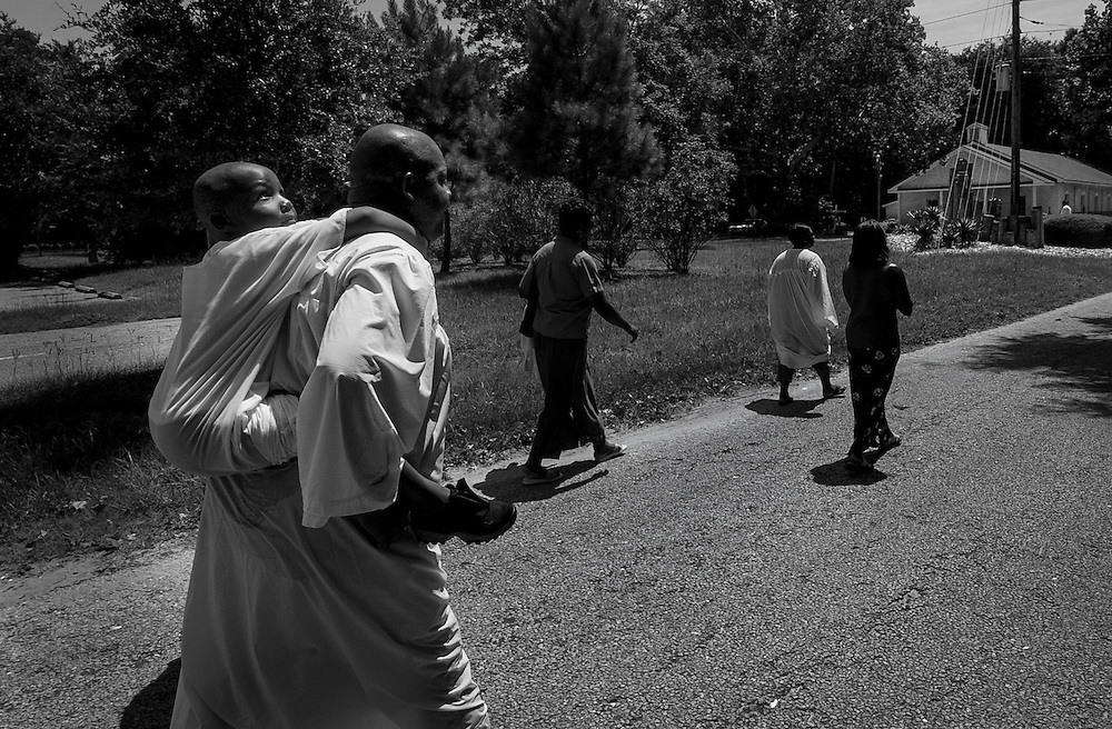 A man carries his son back to the Mt. Calvary Missionary Baptist Church following his baptism in a traditional Gullah Geechee river ceremony on Hilton Head Island.