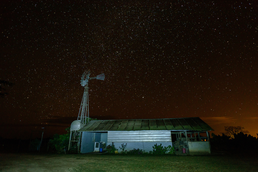 Mennonite farm with windmill under a sky full of stars in Little Belize, Belize.