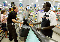"John Madut (cq) (right) rings up the groceries of Stephen Kagan and his daughter Juliana (both cq) at the Toco Hills Publix on Friday, Sept. 1, 2006. One of the ""Lost Boys of Sudan,"" Madut has worked at the grocery store since 2003. This year he returned to Sudan for the first time since leaving and saw that his home town is in desperate need of clean drinking water. He's trying to help by raising funds for a new well, but has found the effort to be a financially monumental task."