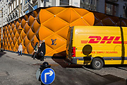 A DHL delivery courier van drives past the temporary renovation hoarding of luxury brand Louis Vuitton in New Bond Street, on 25th February 2019, in London, England.