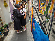 06 FEBRUARY 2015 - BANGKOK, THAILAND: Thai university students check their smart phone near a mural on a wall in the neighborhood near Santa Cruz Church in the Thonburi section of Bangkok. The neighborhood around the church is known for the Thai adaptation of Portuguese cakes baked in the neighborhood. Several hundred Siamese (Thai) Buddhists converted to Catholicism in the 1770s. Some of the families started baking the cakes. When the Siamese Empire in Ayutthaya was sacked by the Burmese, the Portuguese and Thai Catholics fled to Thonburi, in what is now Bangkok. The Portuguese established a Catholic church near the new Siamese capital. There are still a large number of Thai Catholics living in the neighborhood around the church.       PHOTO BY JACK KURTZ