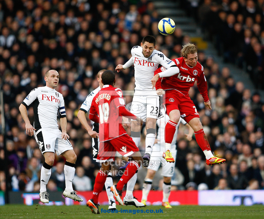 Picture by Andrew Tobin/Focus Images Ltd. 07710 761829.. 07/01/12. Clint Dempsey (23) of Fulham challenges for a high ball with Danny Green (7) of Charlton Athletic during the FA Cup third round match between Fulham and Charlton Athletic at Craven Cottage stadium, London.