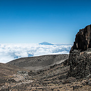The summit of Mt Meru pokes through through the clouds as seen from Arrow Glacier on Mt Kilimanjaro's Lemosho Route.