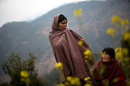 """Sauri, left, and her sister-in-law Birma, reflect in the spot where Sauri's 17-year-old daughter Laxmi burned to death nine months before while sleeping in a chaupadi shed in an area far from the family's home near Dhakari village, Achham, Nepal. """"I have many daughters,"""" said Sauri, """"but she was the one who was always with me."""" The family since destroyed the shed."""