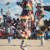 Shannus Becenti, left, dances to the first song for the teen jingle dress pow wow dancers at the Northern Navajo Nation Fair in Shiprock Saturday.