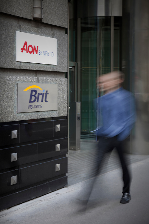 one office worker walking past brit and aon offices in city of london