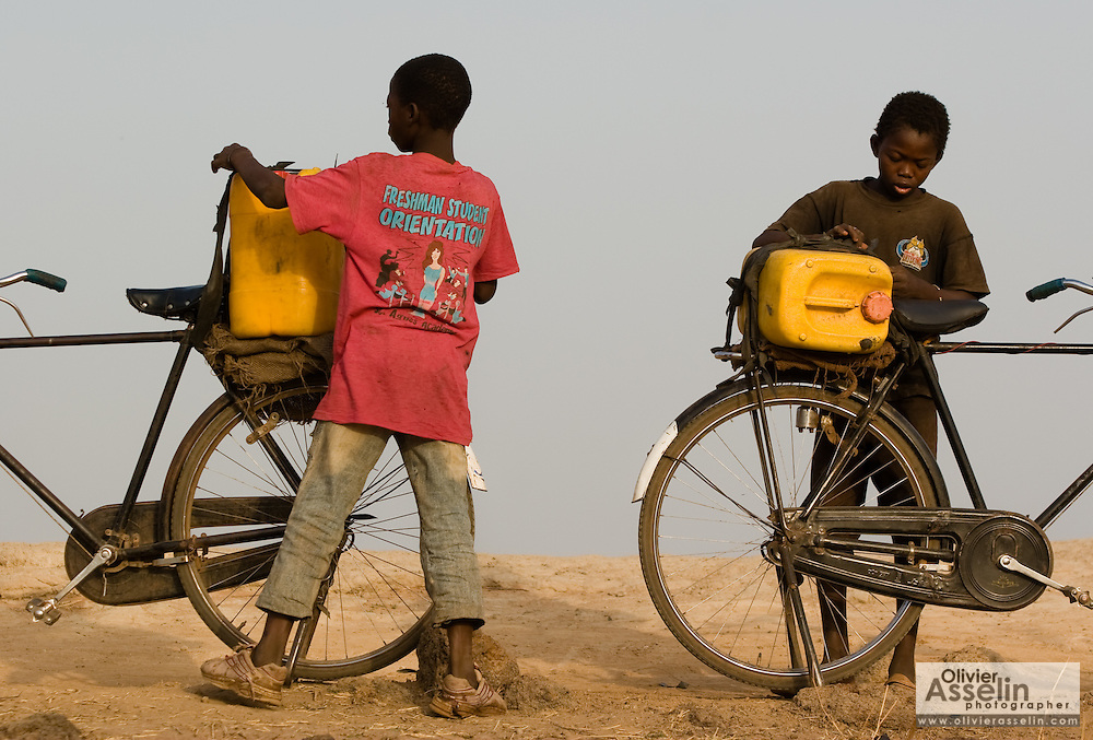 Boys tie plastic containers full of water to the back of their bicycles as they prepare to head home at the Dikunani dam in Savelugu, northern Ghana, on Friday March 9, 2007. The only of four water sources that has not completely dried out around Savelugu, the pond is used by hundreds of people daily who sometimes walk several kilometers to fetch water. Despite the presence of mesh filters available to people who come get water, cases of guinea worm in the area have gone up sharply in the recent months.