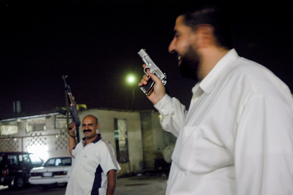 Iraqis celebrating the lifting of more than 13 years of UN embargo against the country by shooting their weapons in the air.<br /> Basra, Iraq. 22/05/2003.