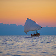 A traditional dhow sailing at sunset on Lake Malawi
