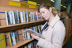 Young woman looking at a DVD in a library,
