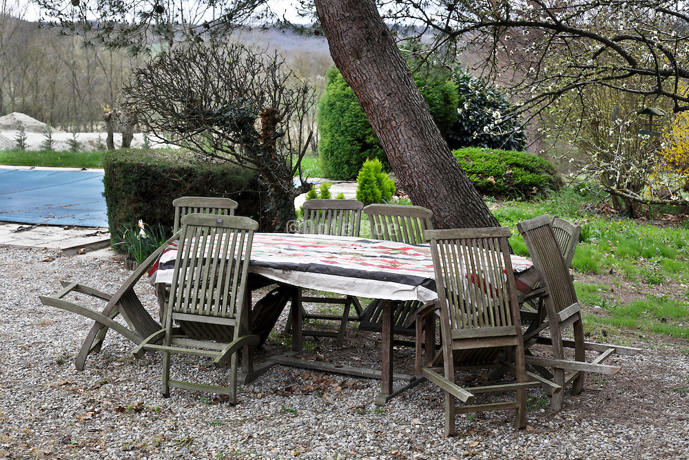 family table and chairs in garden with a closed up swimming pool during early spring season